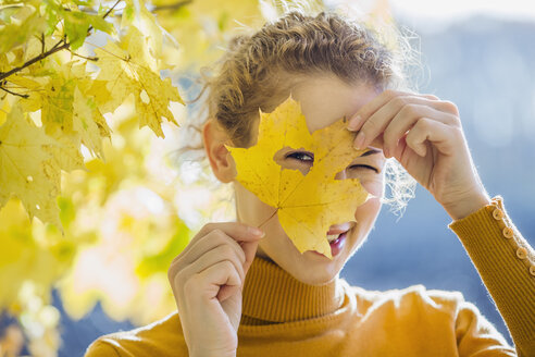 A woman looking through a hole in a leaf she's holding up to her face - FSIF00536