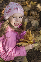 A young girl holding a bunch of autumn leaves - FSIF00539