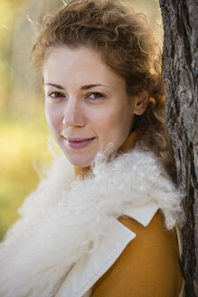 A beautiful woman leaning against a tree in autumn - FSIF00542