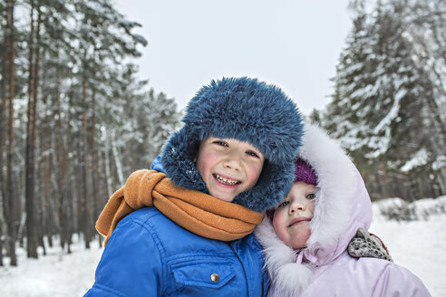 A cheerful brother and sister in warm winter clothing outdoors in winter - FSIF00605