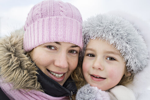 A cheerful mother and daughter in warm clothing outdoors in winter - FSIF00608