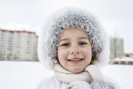 A cheerful young girl wearing warm clothing outdoors in winter - FSIF00611