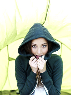 A teenage girl sitting in a tent pulling the sides of her hood sweatshirt together - FSIF00617
