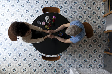 A mixed age couple holding hands at the breakfast table, directly above - FSIF00626