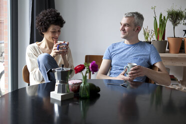 A cheerful hip mixed age couple enjoying breakfast together in their dining room - FSIF00632