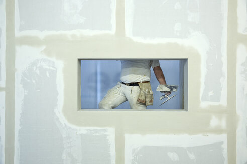 A house painter holding a trowel, seen through window hole in a newly constructed wall - FSIF00653