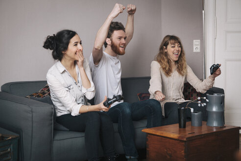 Excited young friends playing video games at home - FSIF00887