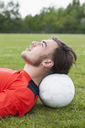 Side view of young man resting head on soccer ball in field - FSIF00902
