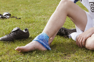 Low section of soccer player applying ice pack on ankle in field - FSIF00905