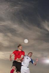 Male soccer players heading ball against sky - FSIF00911