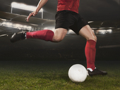 Low section of young soccer player kicking ball on field - FSIF00917