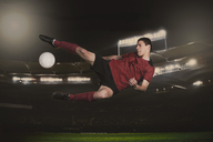 Full length of soccer player kicking ball during match - FSIF00926