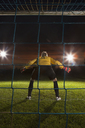 Full length rear view of goalie defending soccer net on field - FSIF00929
