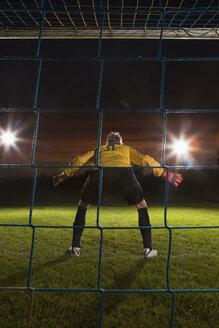Full length rear view of goalie defending soccer net on field - FSIF00929