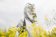 A person in a radiation protective suit standing in an oilseed rape field - FSIF00932