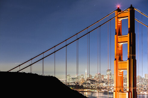 Golden Gate Bridge with illuminated cityscape in background - FSIF00986