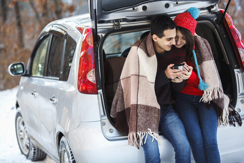 Happy young couple having coffee while sitting in boot of car during winter - FSIF00989