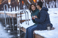 Happy young couple having coffee while sitting on pier - FSIF00992