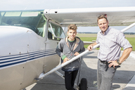 Portrait of happy father and son standing outside private airplane - FSIF01004