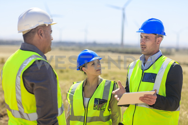 Three engineers with tablet discussing on a wind farm - ZEF14955