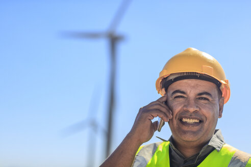 Portrait of smiling technician on cell phone on a wind farm - ZEF14958