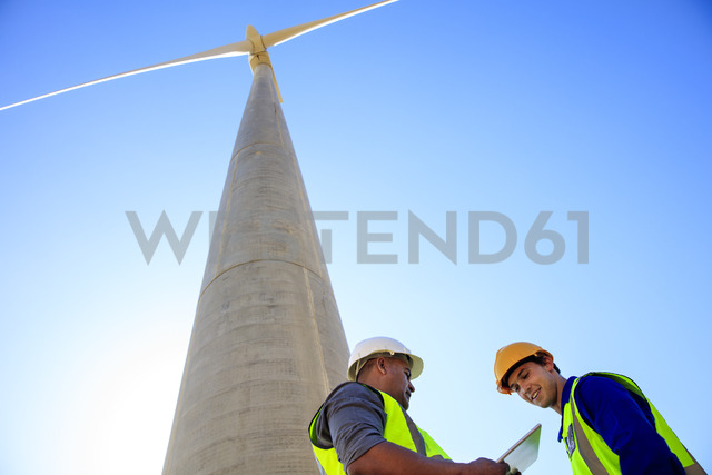 Low angle view of technicians with tablet in front of wind turbine - ZEF14964