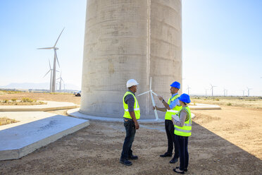 Three engineers with wind turbine model discussing on a wind farm - ZEF14967