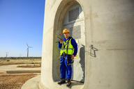Technician holding walkie-talkie at wind turbine - ZEF14970