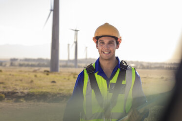 Portrait of smiling technician on a wind farm - ZEF14976