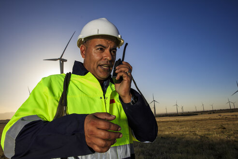 Technician using walkie-talkie on a wind farm - ZEF14979