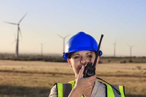 Female technician using walkie-talkie on a wind farm - ZEF14982