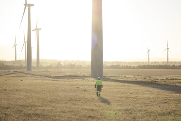 Engineer walking on a wind farm at sunset - ZEF14985