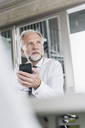 Mature businessman with cell phone at desk in office thinking - UUF12732