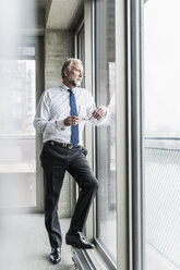 Serious mature businessman standing at the window looking out - UUF12738