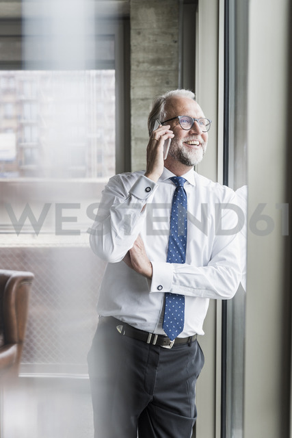 Happy mature businessman standing at the window talking on cell phone - UUF12741