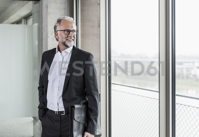 Smiling mature businessman standing at the window looking out - UUF12753