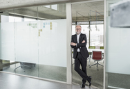 Portrait of confident mature businessman standing in office - UUF12756