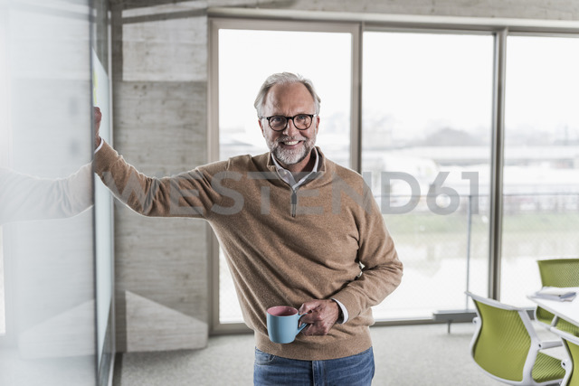 Portrait of smiling casual mature businessman standing in office - UUF12762