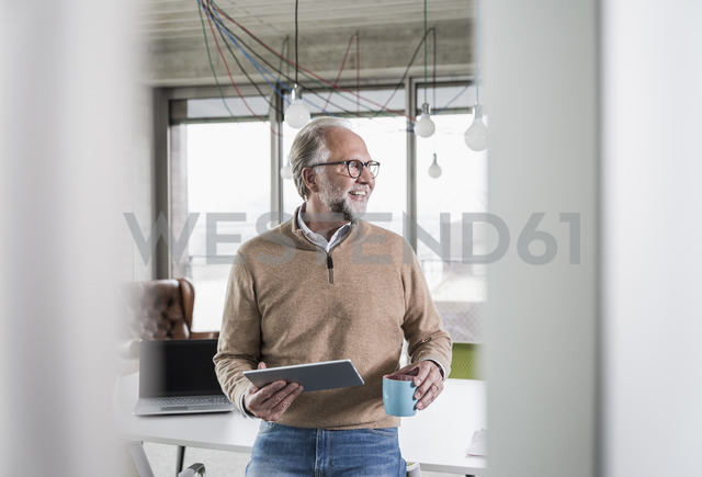 Smiling casual mature businessman holding tablet and cup of coffee in conference room in office - UUF12768
