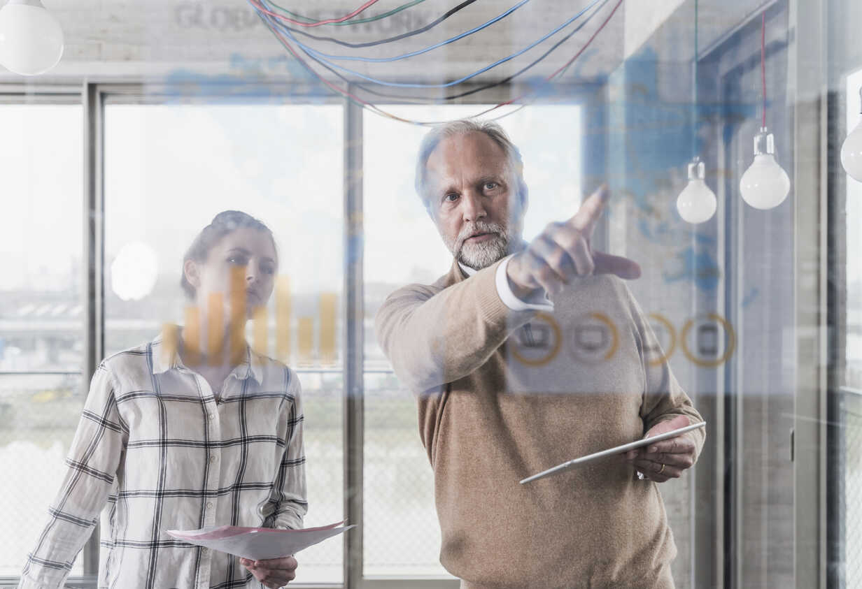 Casual mature businessman and young woman discussing data at glass pane in office - UUF12774 - Uwe Umstätter/Westend61