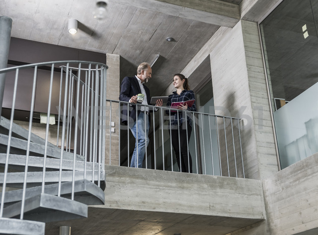 Smiling mature businessman and young woman talking in staircase - UUF12783