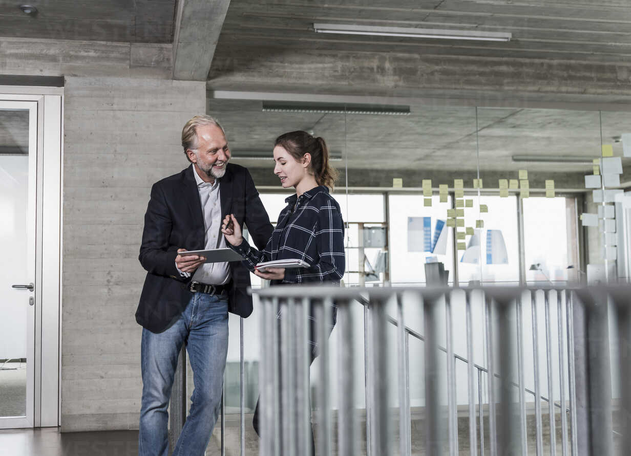 Smiling mature businessman and young woman talking in staircase - UUF12786 - Uwe Umstätter/Westend61
