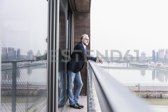 Mature businessman standing on balcony - UUF12792