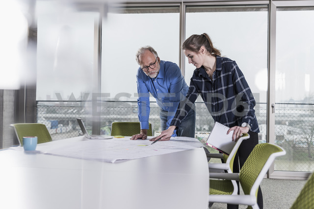 Mature businessman and young woman talking in conference room in office - UUF12795