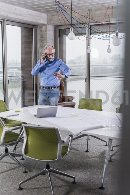 Mature businessman talking on smartphone in conference room in office - UUF12801