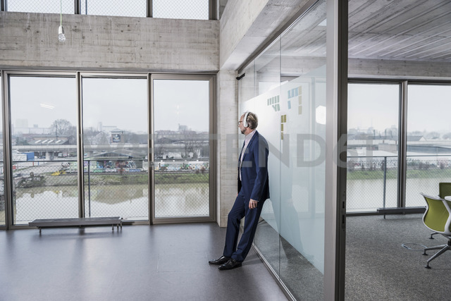 Mature businessman listening to music on headphones looking out of window - UUF12810