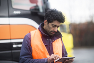 Man wearing reflective vest using tablet at trucks - SGF02185