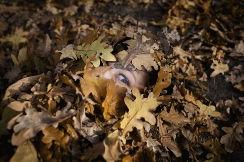 Close-up portrait of woman covered in dry leaves during autumn - FSIF01041