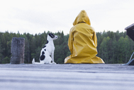 Rear view of woman wearing yellow raincoat sitting with dog on jetty at forest - FSIF01050