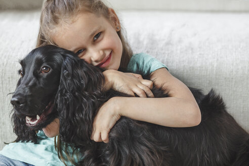 Portrait of smiling girl embracing dog at home - FSIF01062